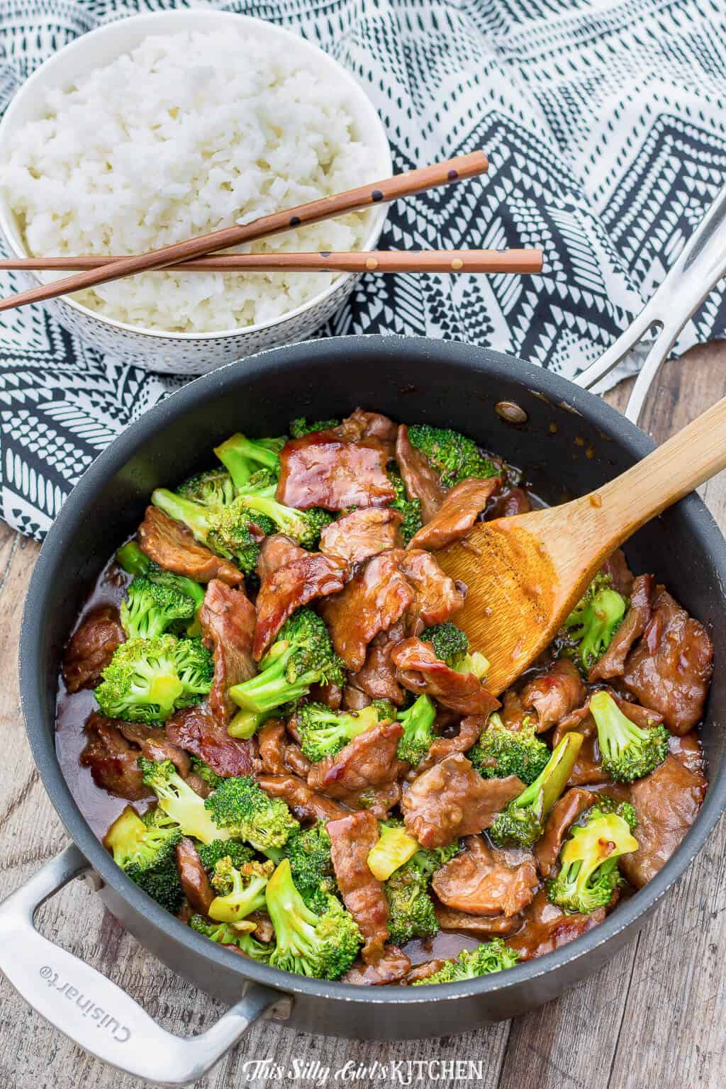 Overhead photo fo Beef and Broccoli in pan with bowl of white rice and chopsticks