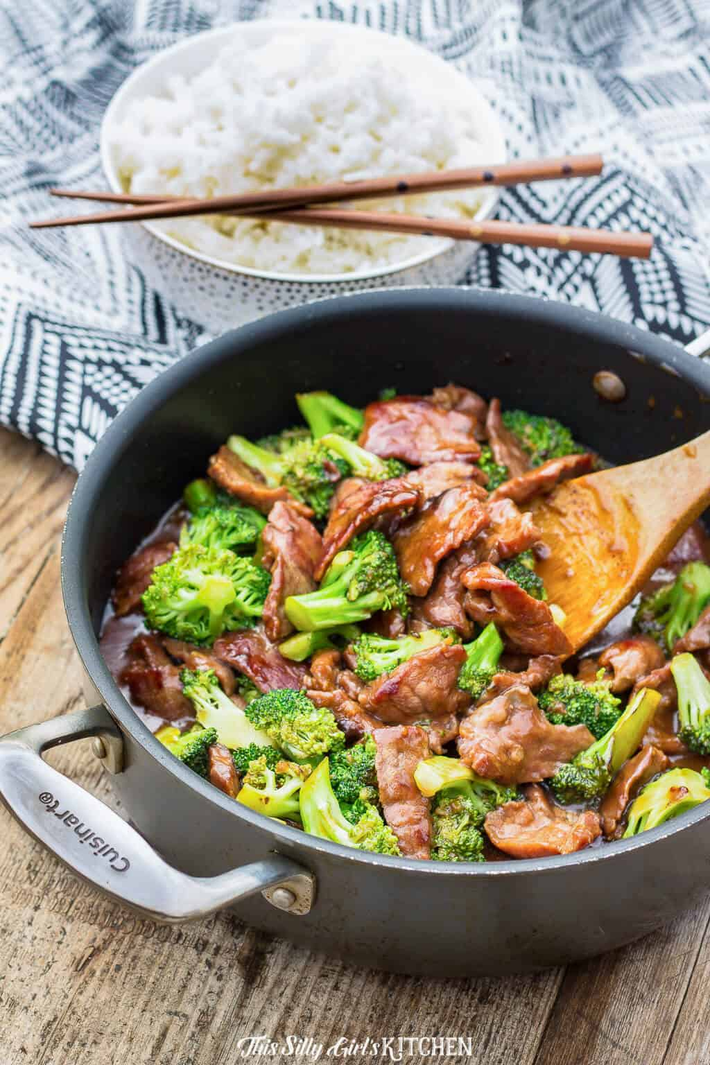 Beef and Broccoli in pan with bowl of rice in background
