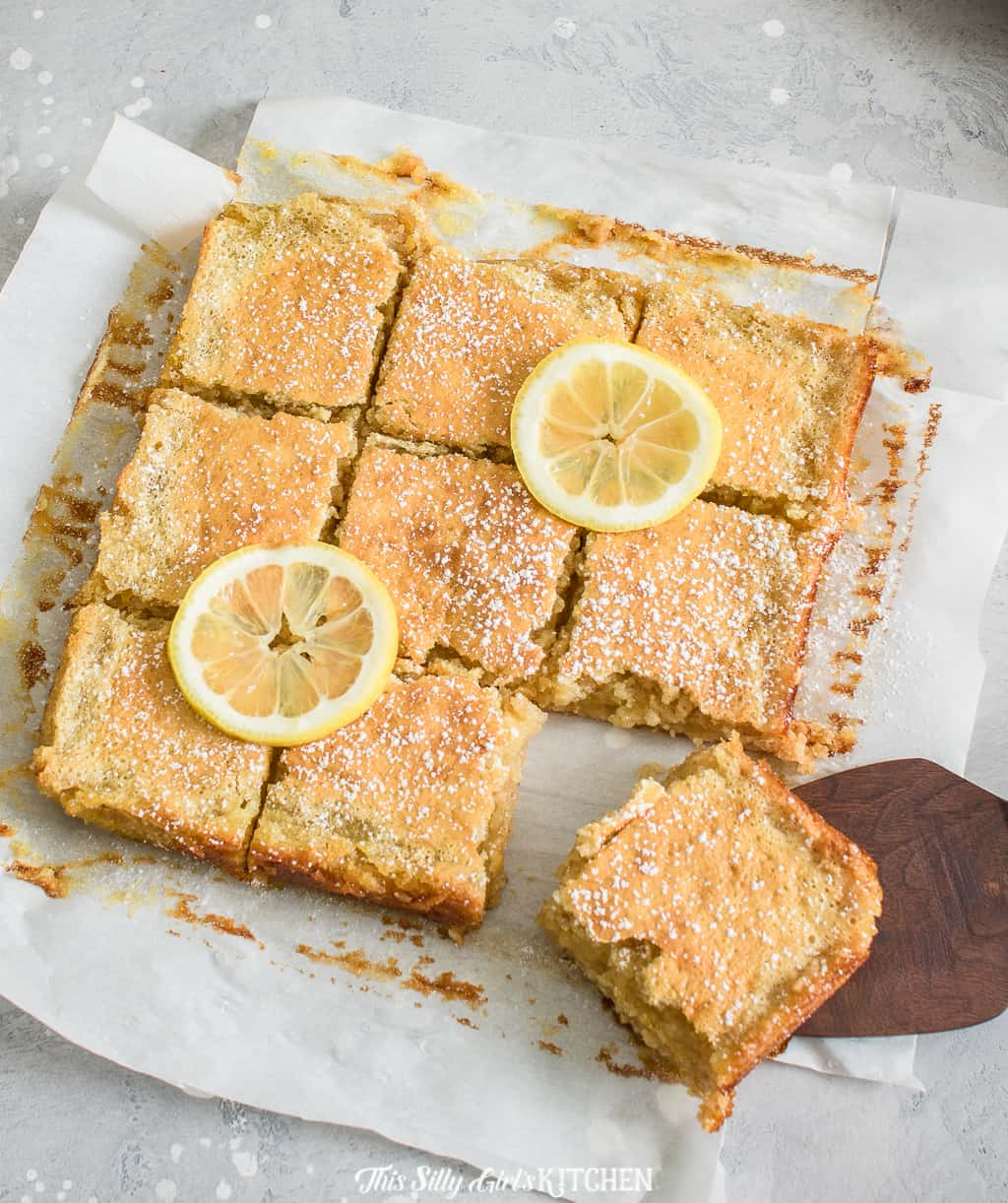 Gooey lemon bars are bursting with bright citrusy flavors, perfect for summer. #Recipe from ThisSillyGirlsKitchen.com #lemonbars #oatmealbars #almond #lemon