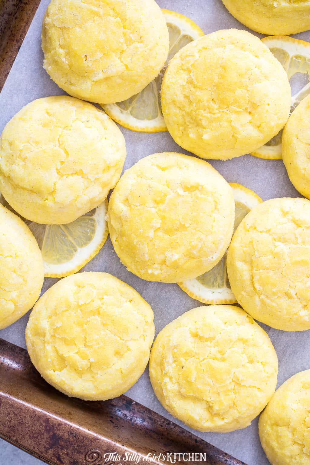 Meltaway Lemon Cookies on sheet pan with lemon slices
