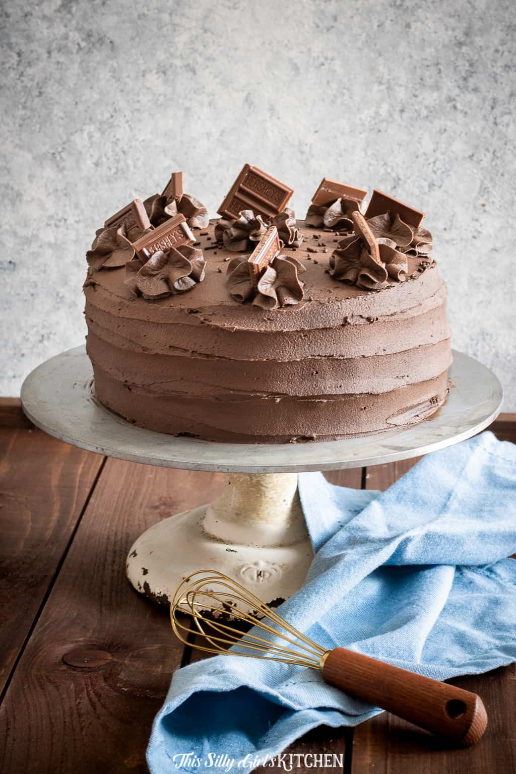 Chocolate Layer Cake on cake stand with whisk