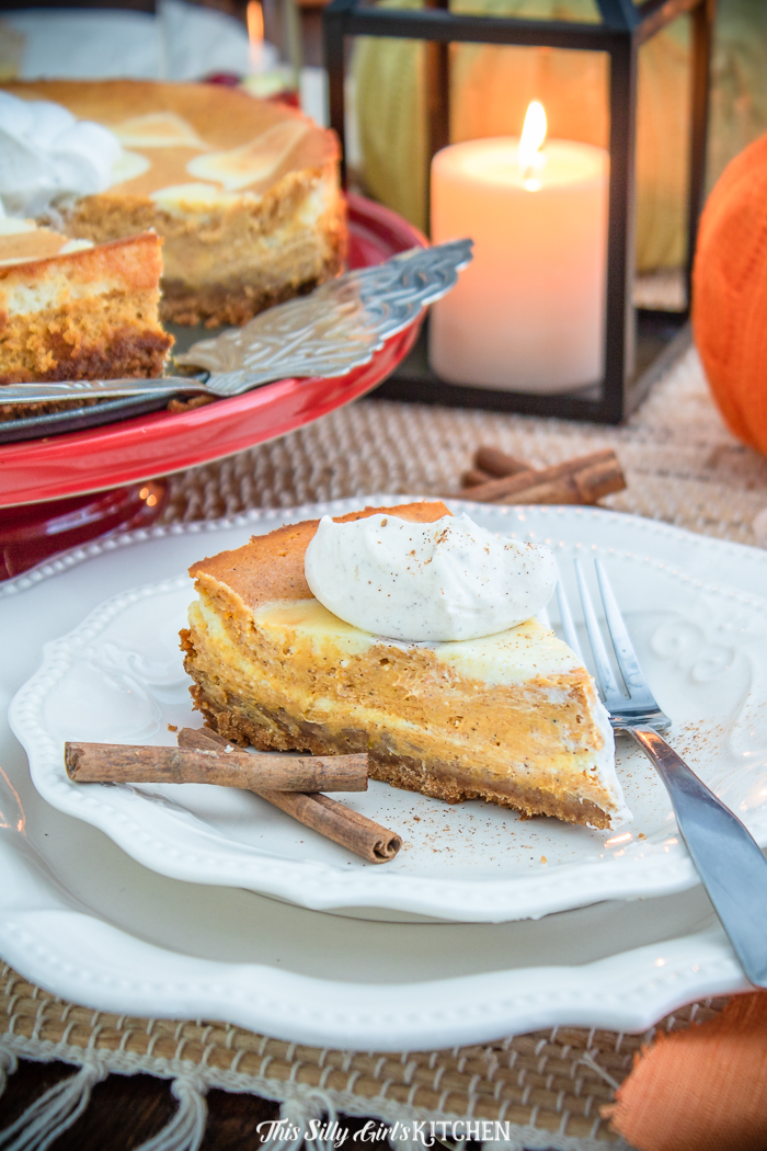 Slice of Pumpkin Cheesecake on white plate with fork and cinnamon sticks