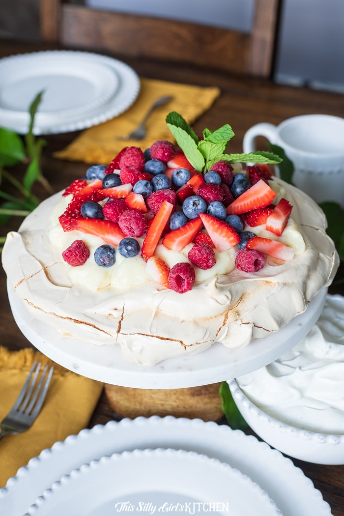 Pavlova topped with pastry cream, berries and mint on cake stand