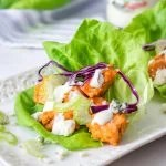 One Chicken Lettuce wrap on white tray up close Square image