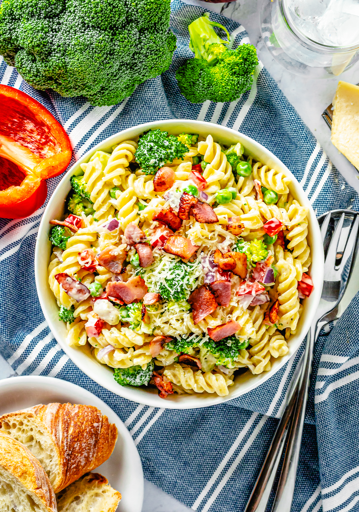 Broccoli Pasta Salad overhead in white bowl with ingredients surrounding bowl