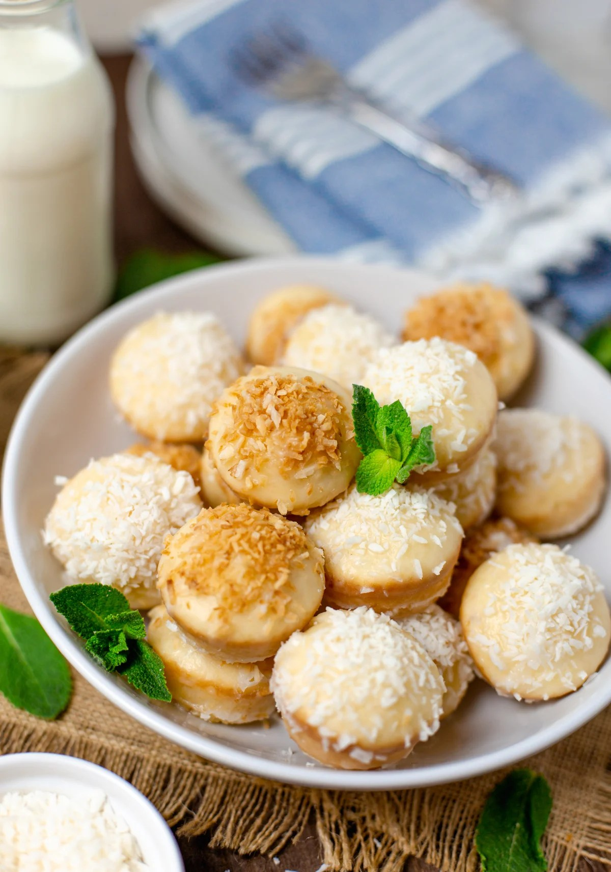 Side view of stacked Baked Coconut Donut Holes in white dish