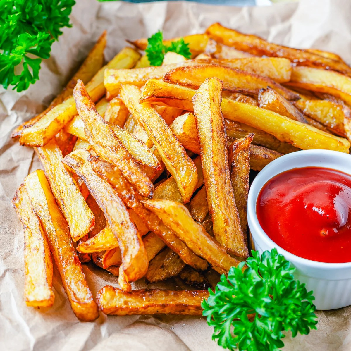 Square image of French Fries on brown parchment with parsley and ketchup.