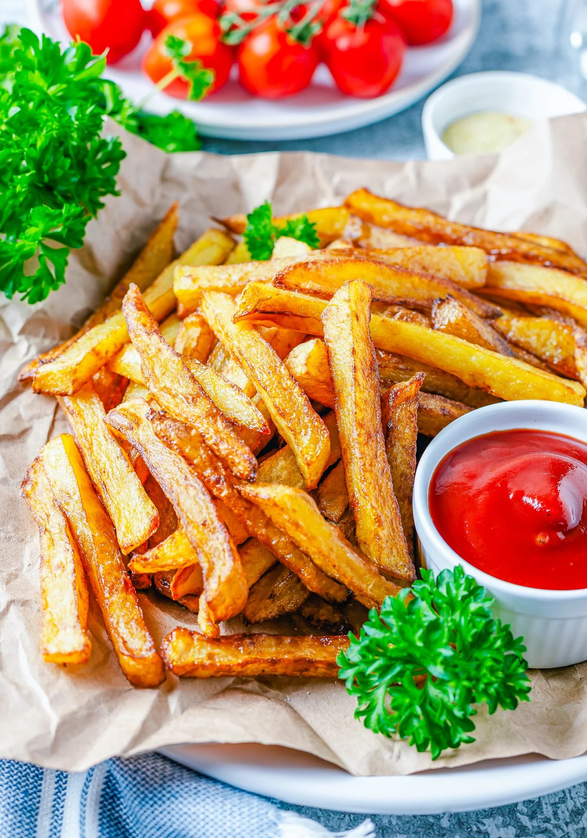 Side view of plated Homemade French Fries with ketchup and parsley.