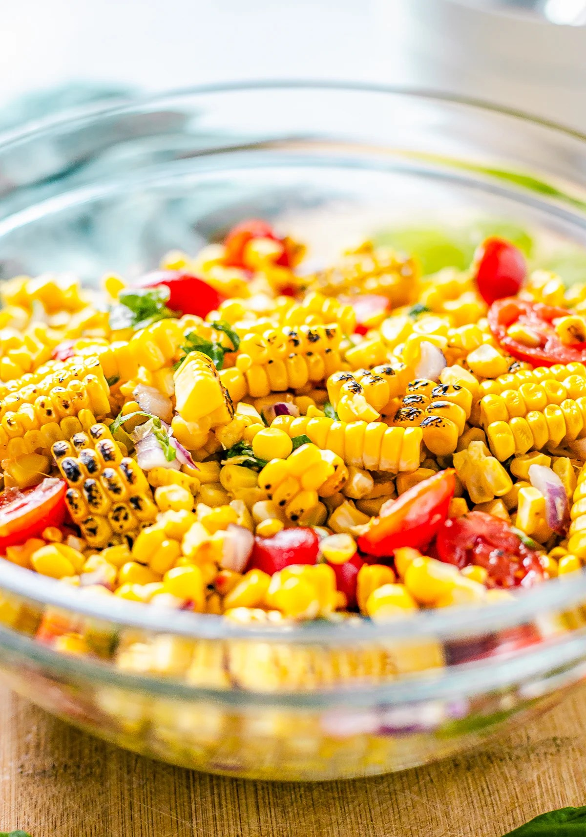 Side view of bowl of Corn and Tomato Salad showing charred corn