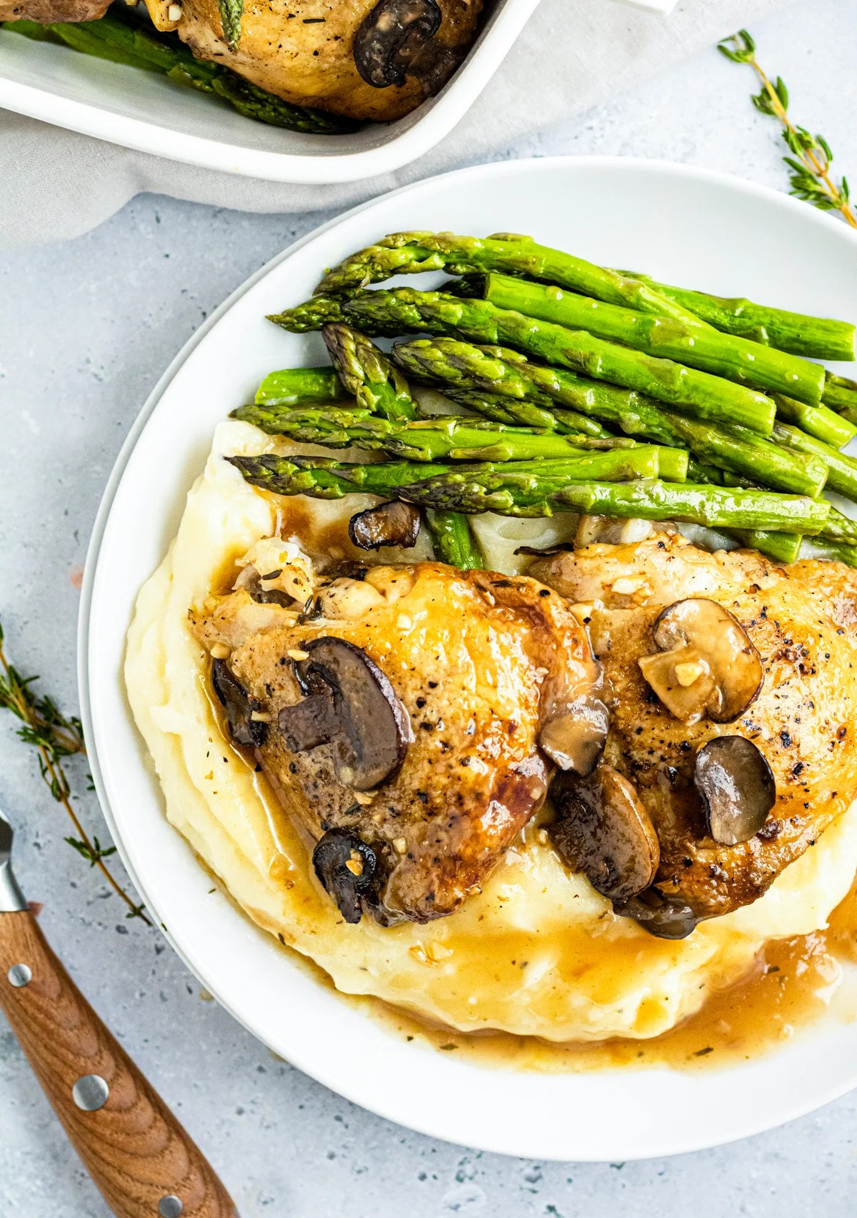 Overhead photos of Marsala Chicken Thighs over potatoes with asparagus