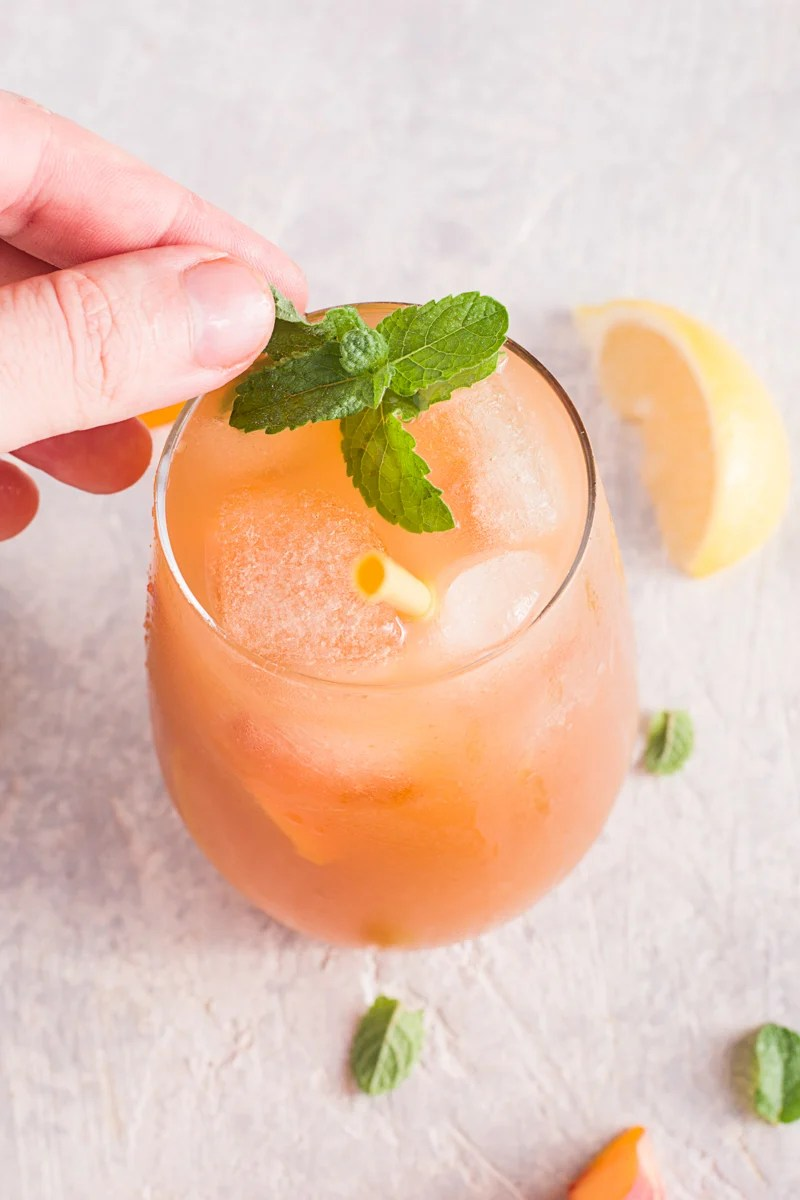 Hand putting a garnish of mint in glass