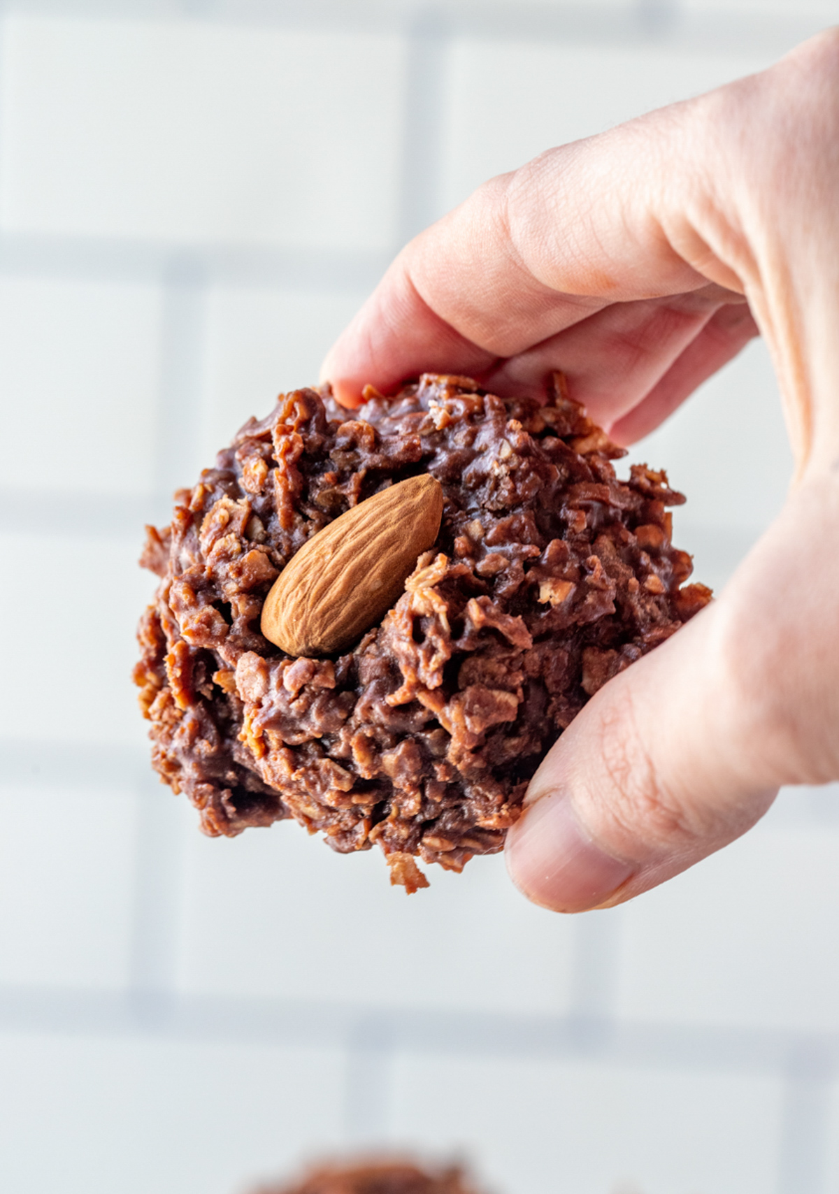 Hand holding one No Bake Almond Joy Cookie