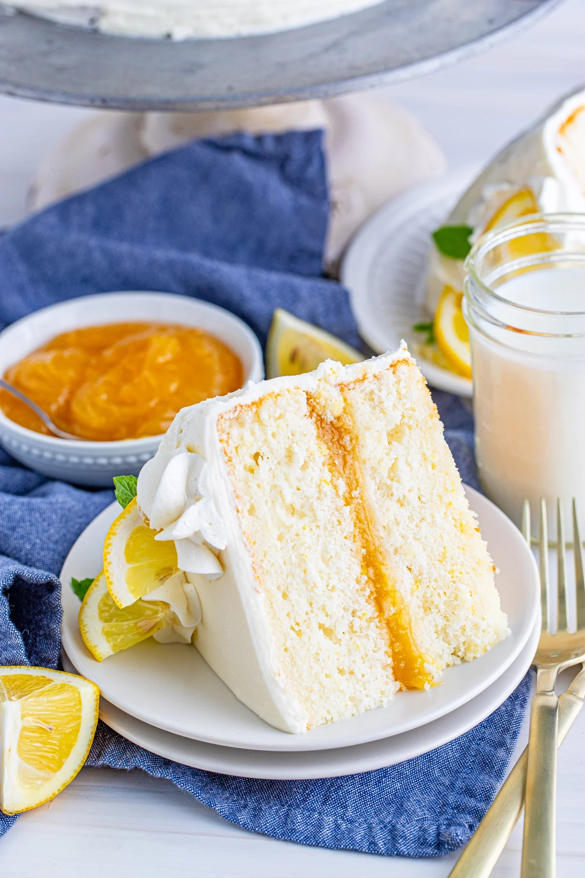 One slice of Lemon Layer Cake on white plate with lemon curd in background