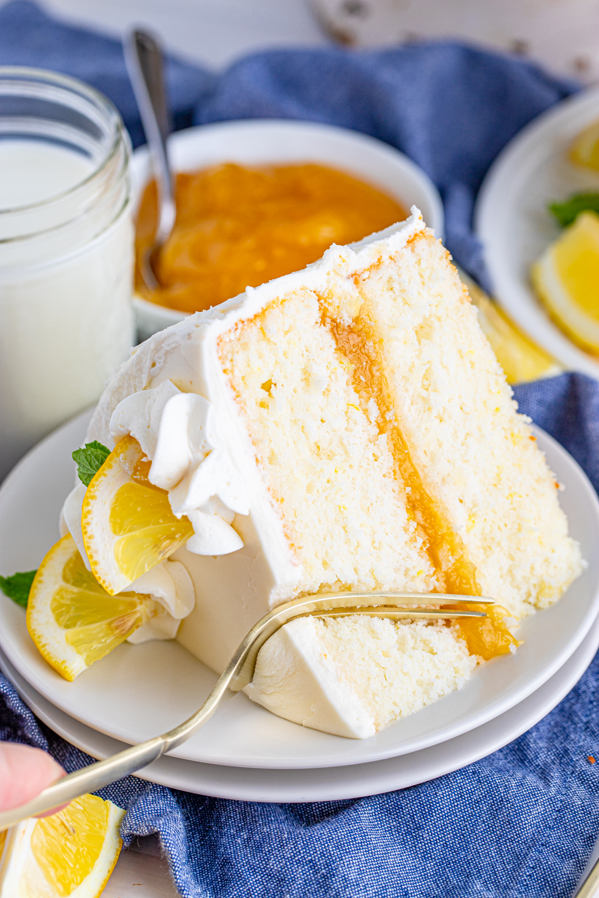 Fork Cutting a bite out of a slice of Lemon Layer Cake