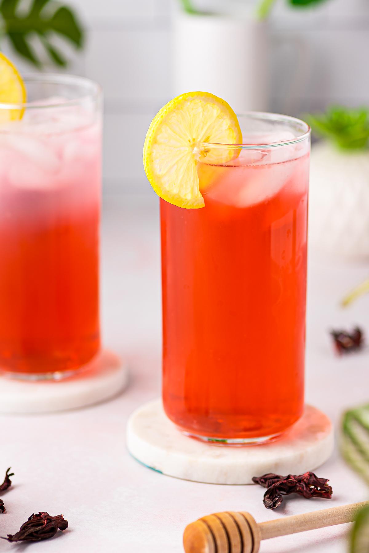 Glass of Hibiscus Tea Recipe garnished with slice of lemon