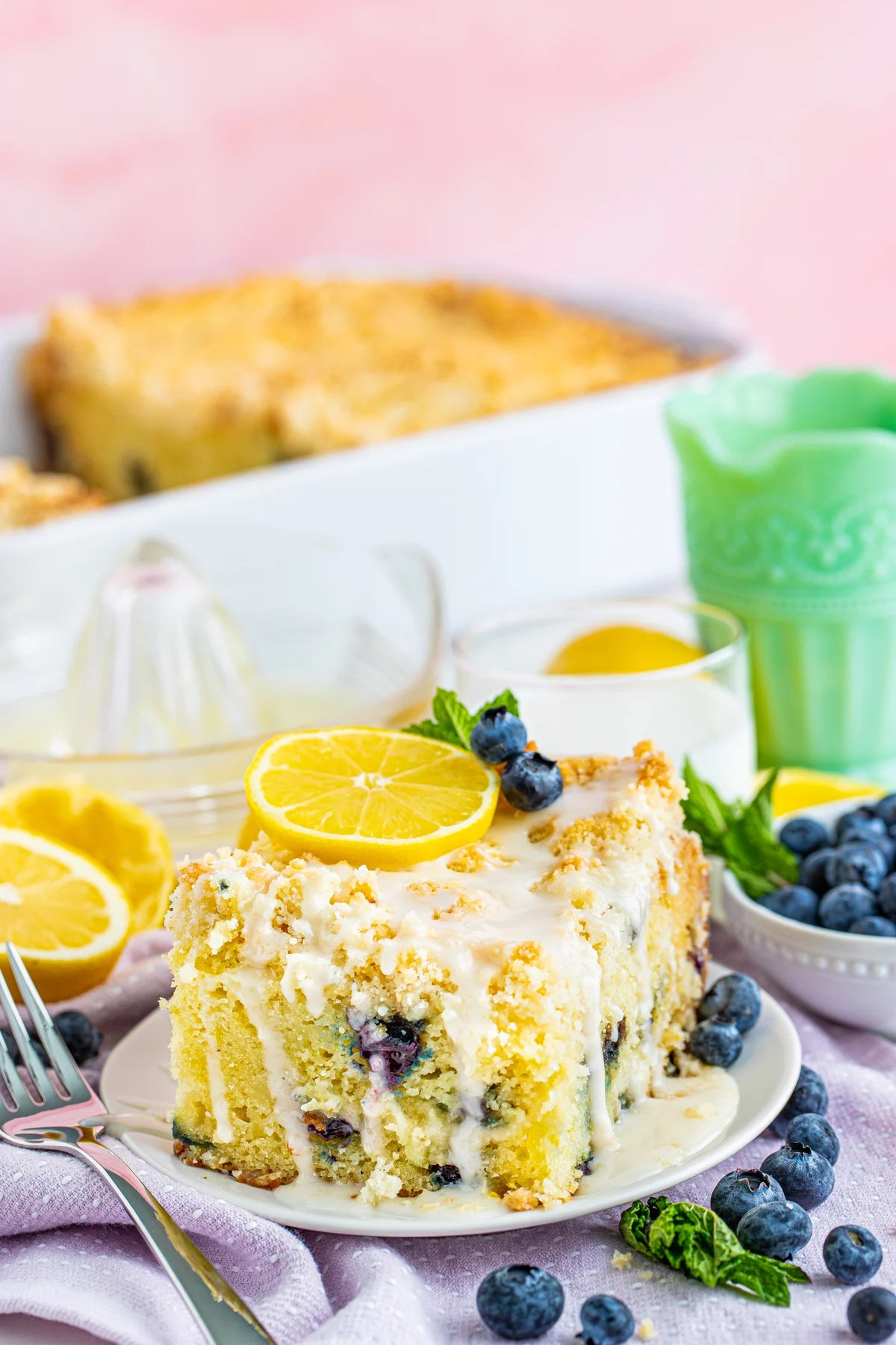Slice of Lemon Blueberry Coffee cake on white plate topped with lemon, blueberries and mint