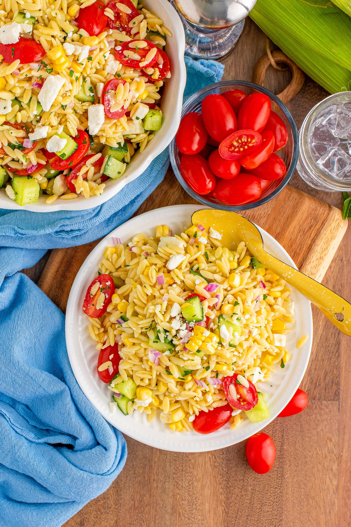 Overhead of the Orzo Pasta Salad on white plate with spoon and ingredients