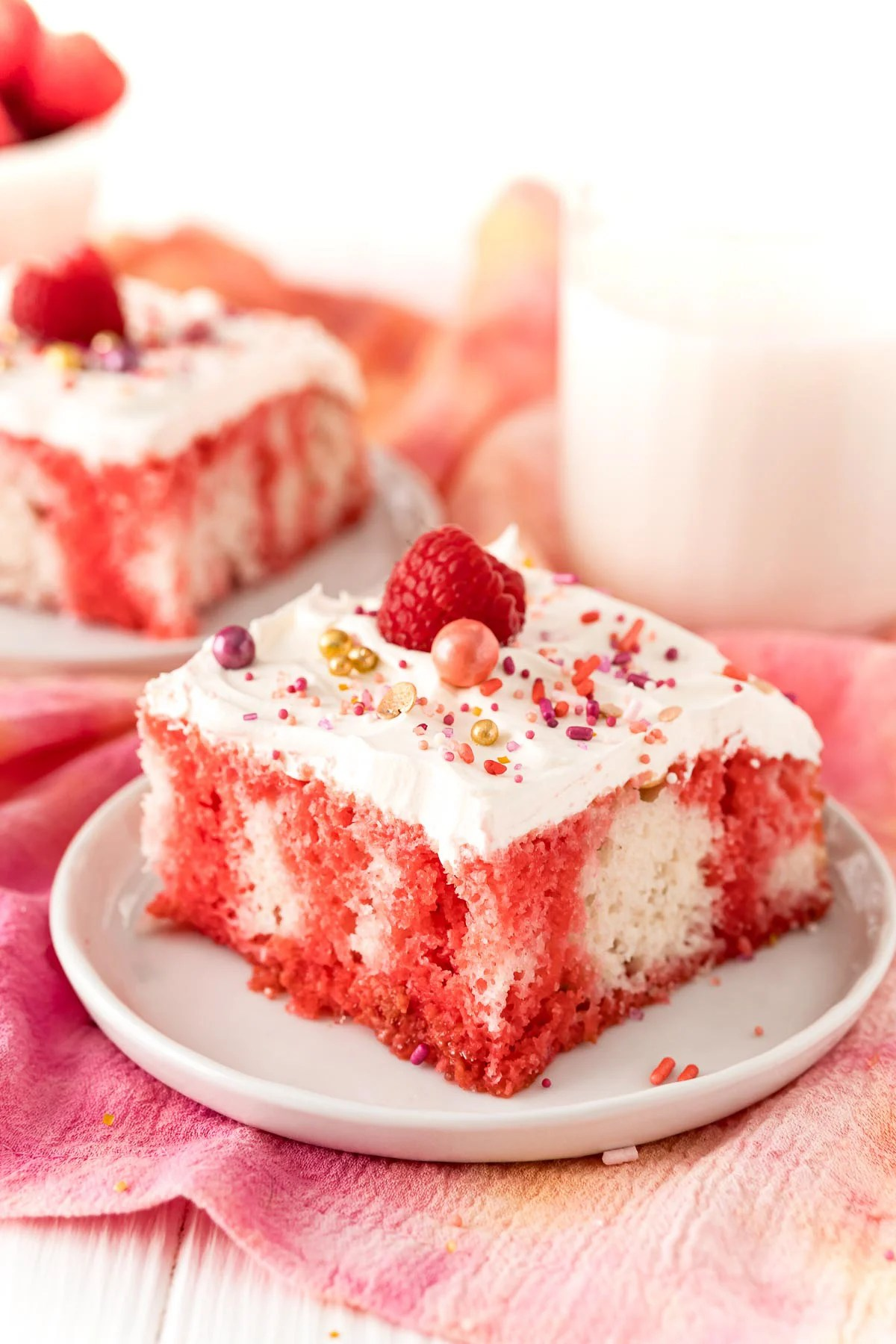 Slice of Raspberry Jello Poke Cake on white plate topped with sprinkles and raspberry