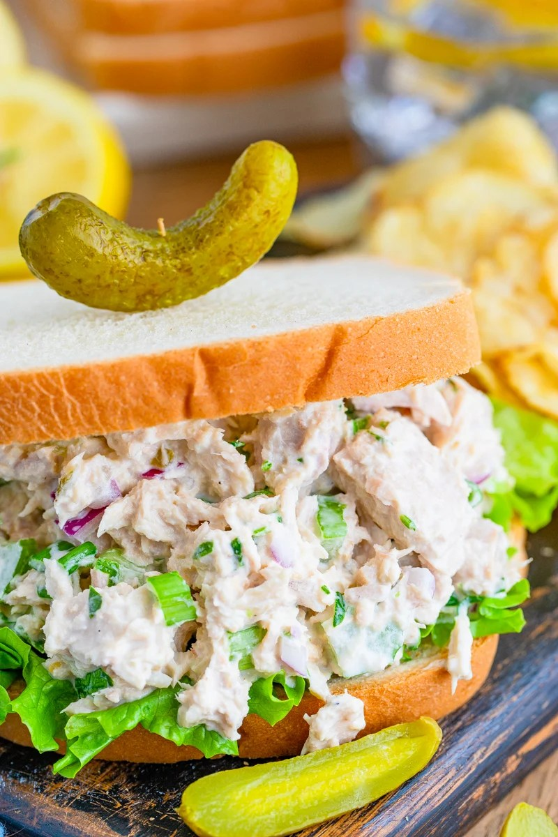 Close up of mixed up Tuna Salad Sandwich on bread topped with a pickle