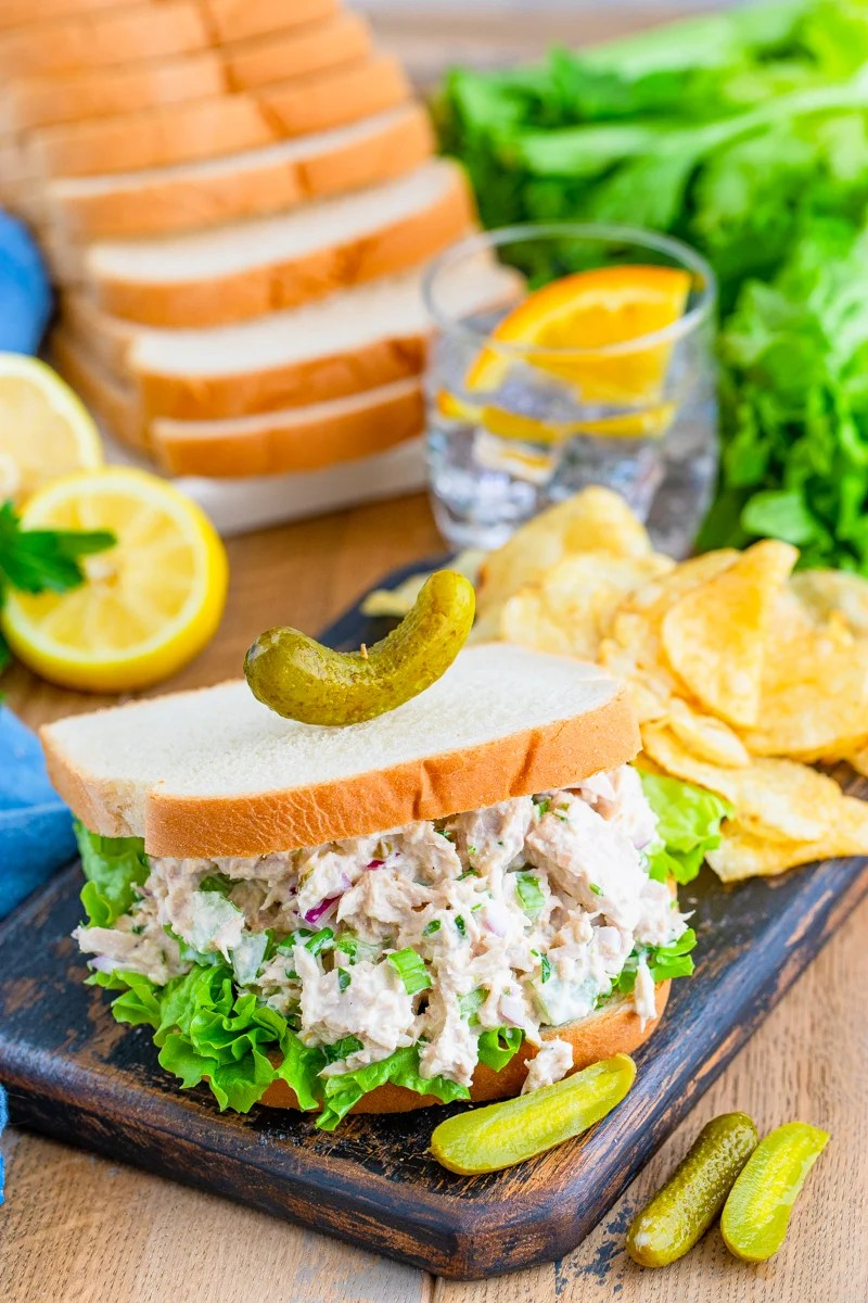 Finished Tuna Salad sandwich on wooden board with chips and bread in background