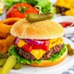 Square close up image of Cheeseburger Recipe on marble platter with onion rings and pickles