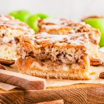 Close up square image of Apple Pie Bars cut on wooden board.