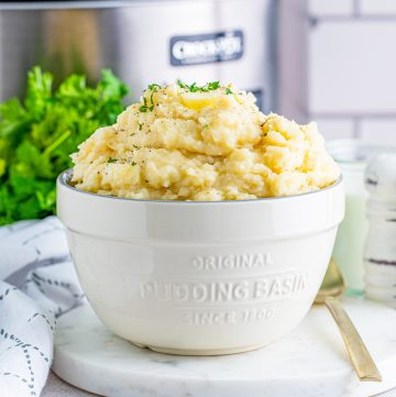 Square image of white serving bowl of Slow Cooker Mashed Potatoes.