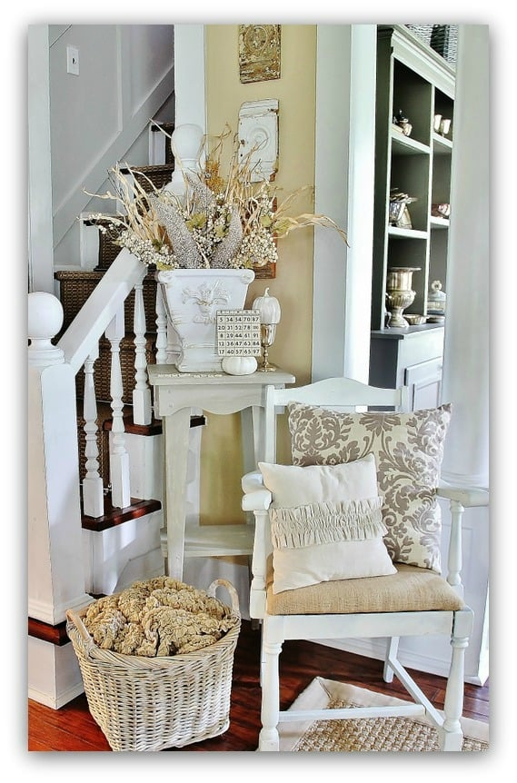 The white painted pumpkin and rustic flowers add to the home's fall decor.