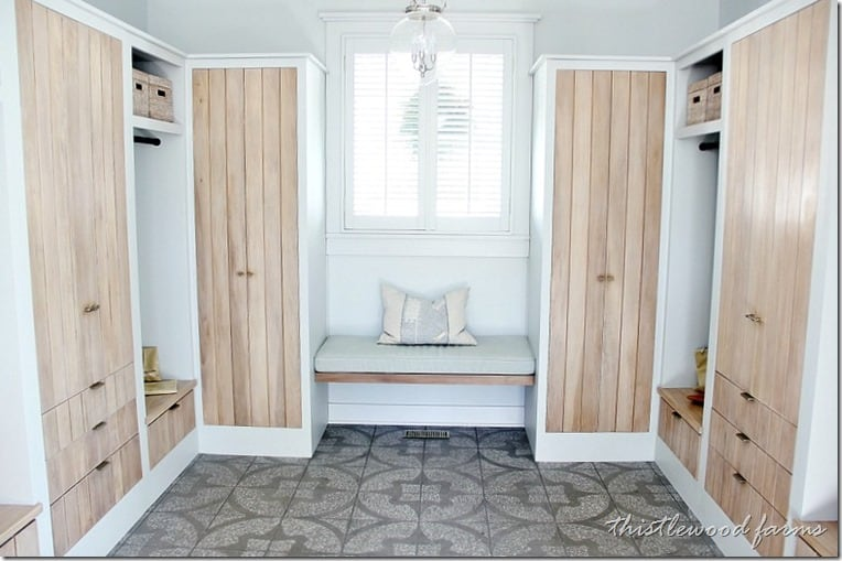 This off-bathroom dressing room has built-in closets with wooden doors and drawers
