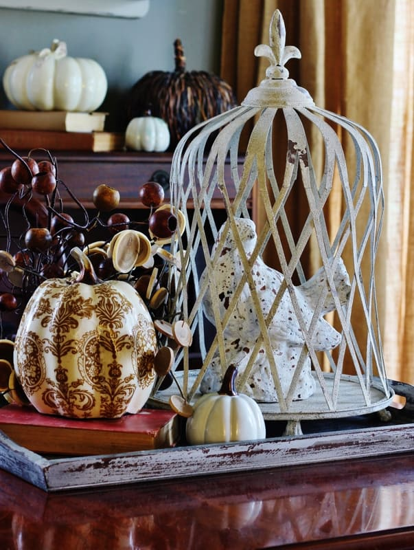 A wooden serving tray with vintage fall decorations