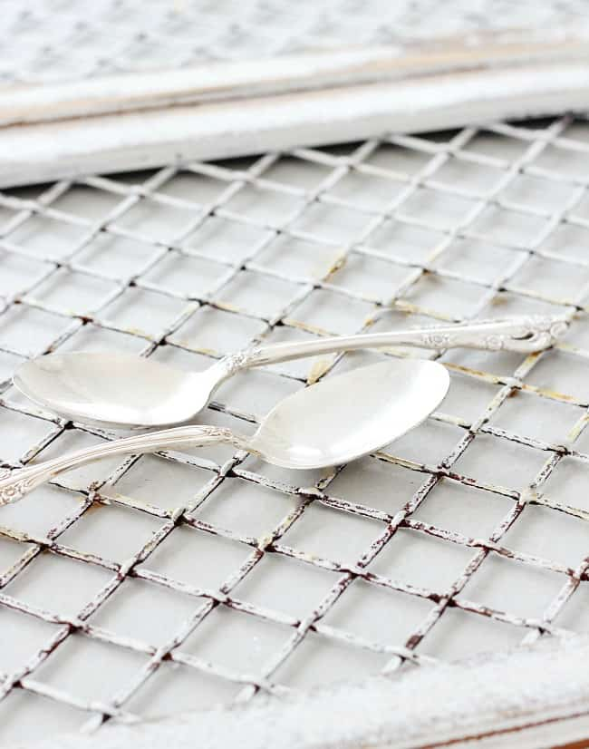 Silver plated spoons sitting on a vintage tray found at a yard sale