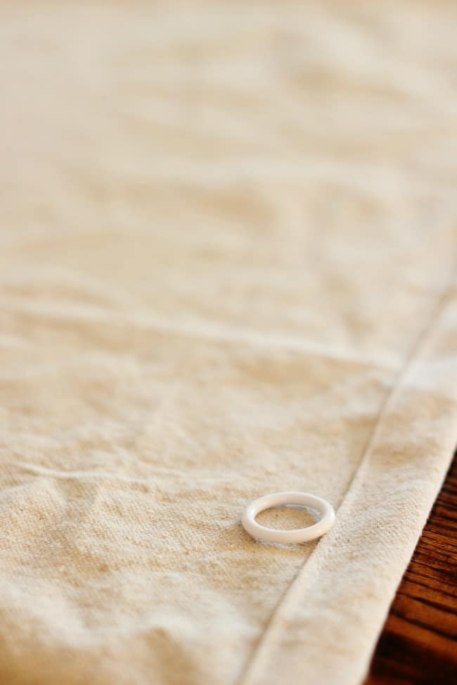 Carefully add rings to the hem of your drop cloth.