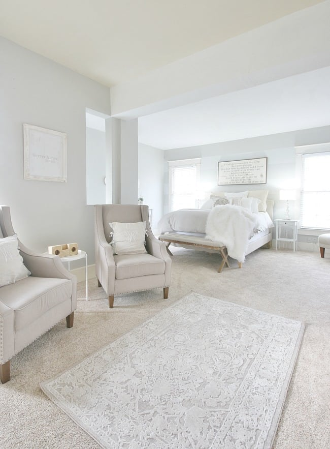 This farmhouse style bedroom has a gray themed sitting area with gray reading chairs, soft lighting from the bedside windows, and a gorgeous gray rug