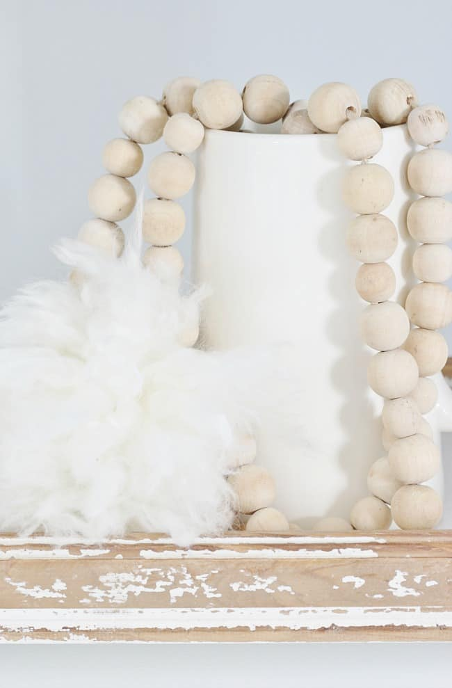 Distressed wood dressed and a white vase with a thread of wooden balls