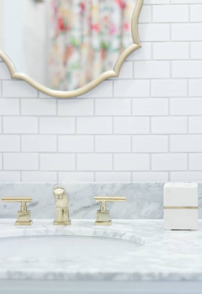 We added brass faucets and gold accents to compliment the white tile and counters.