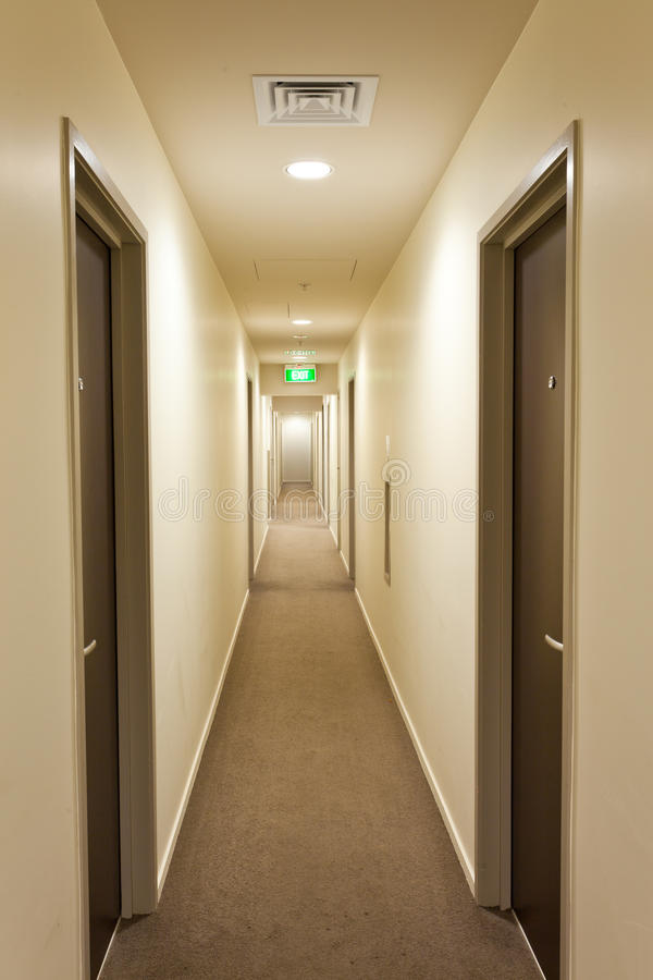 Long Corridor With Hotel Room Doors And Exit Sign Stock