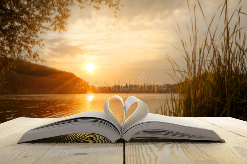 Open Book On Wooden Table On Natural Blurred Background