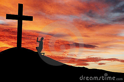 Silhouette Of A Man Praying Under The Cross Royalty Free