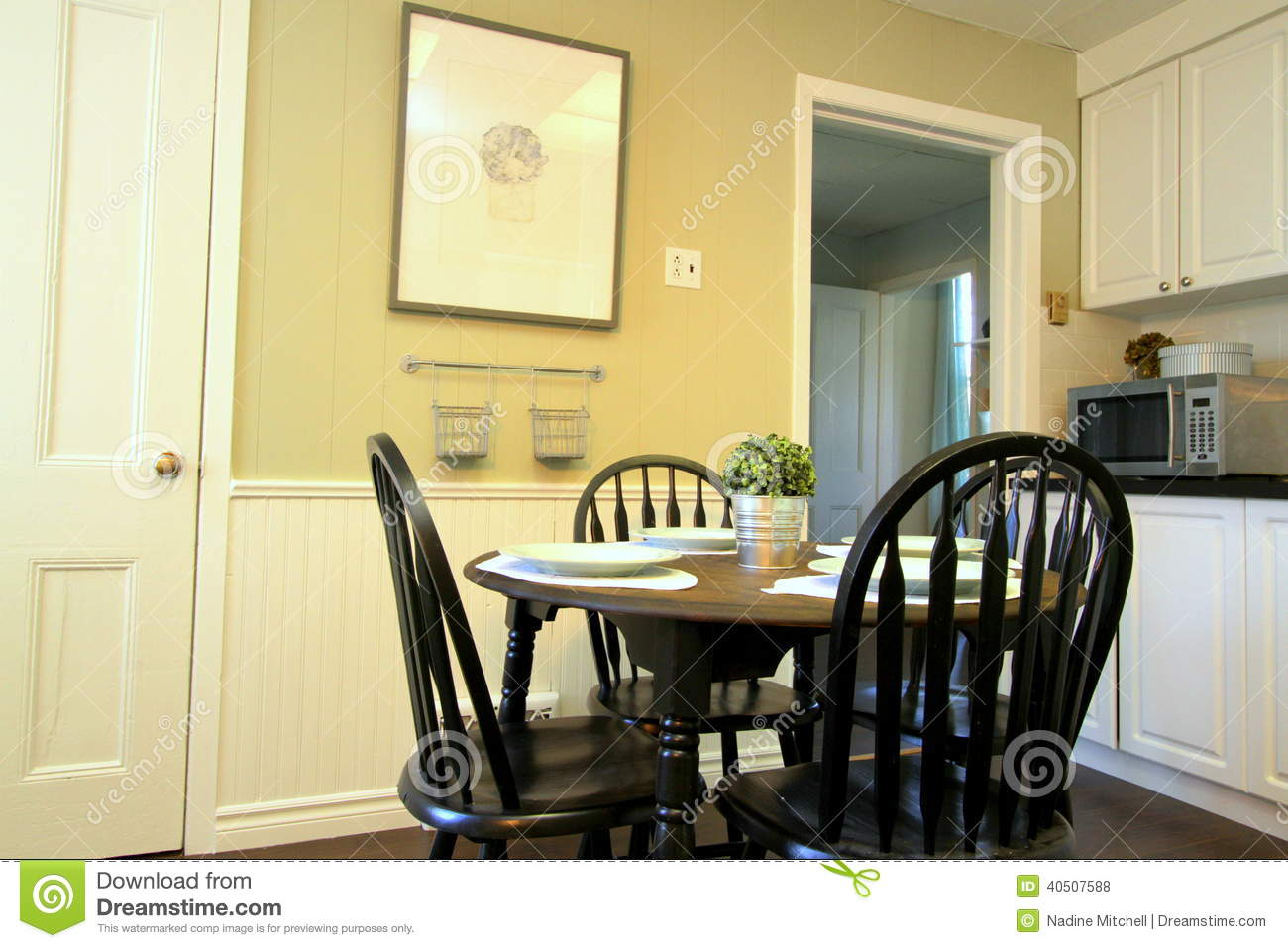 Kitchen With White Cabinets And Round Table And Chairs