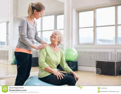 Older Woman Assisted By Personal Trainer At Gym Stock ...