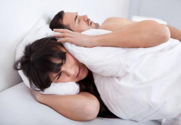 wanita menutup telinga di sebelah suaminya yang sedang tidur