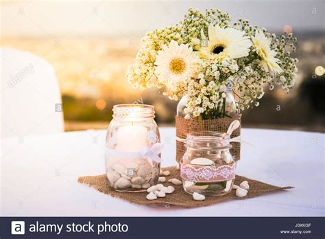 pretty white wedding table decorations flowers candles pebbles
