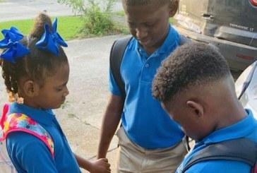 """La foto del primer día de clases de los hermanos orando se vuelve viral: """"Oremos por todos"""""""