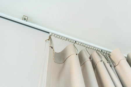 White Curtain Rail System With Light Brown Curtain Installed   Stock     White curtain rail system with light brown curtain installed on white  ceiling Stock Photo   88334233