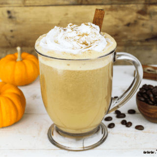 Vegan pumpkin spiced latte is a glass mug. Topped with whipped cream and a cinnamon stick.
