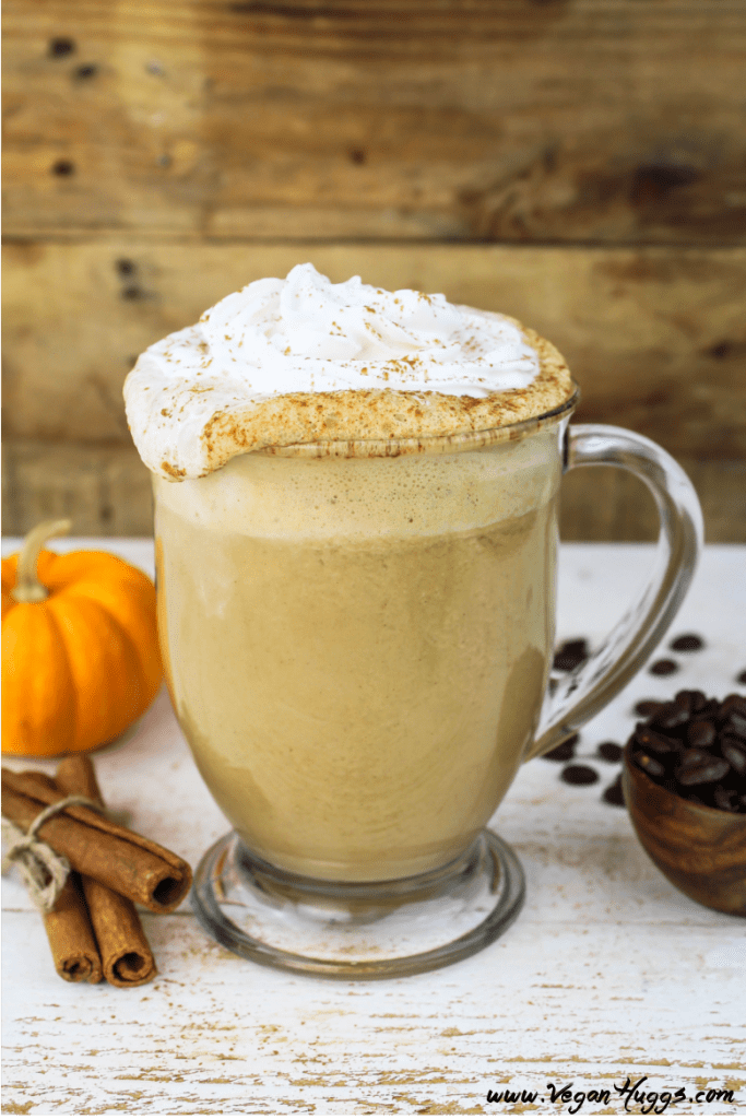 Vegan Pumpkin Spice Latte in a glass mug. Whipped cream spilling over top. Coffee beans on the side.