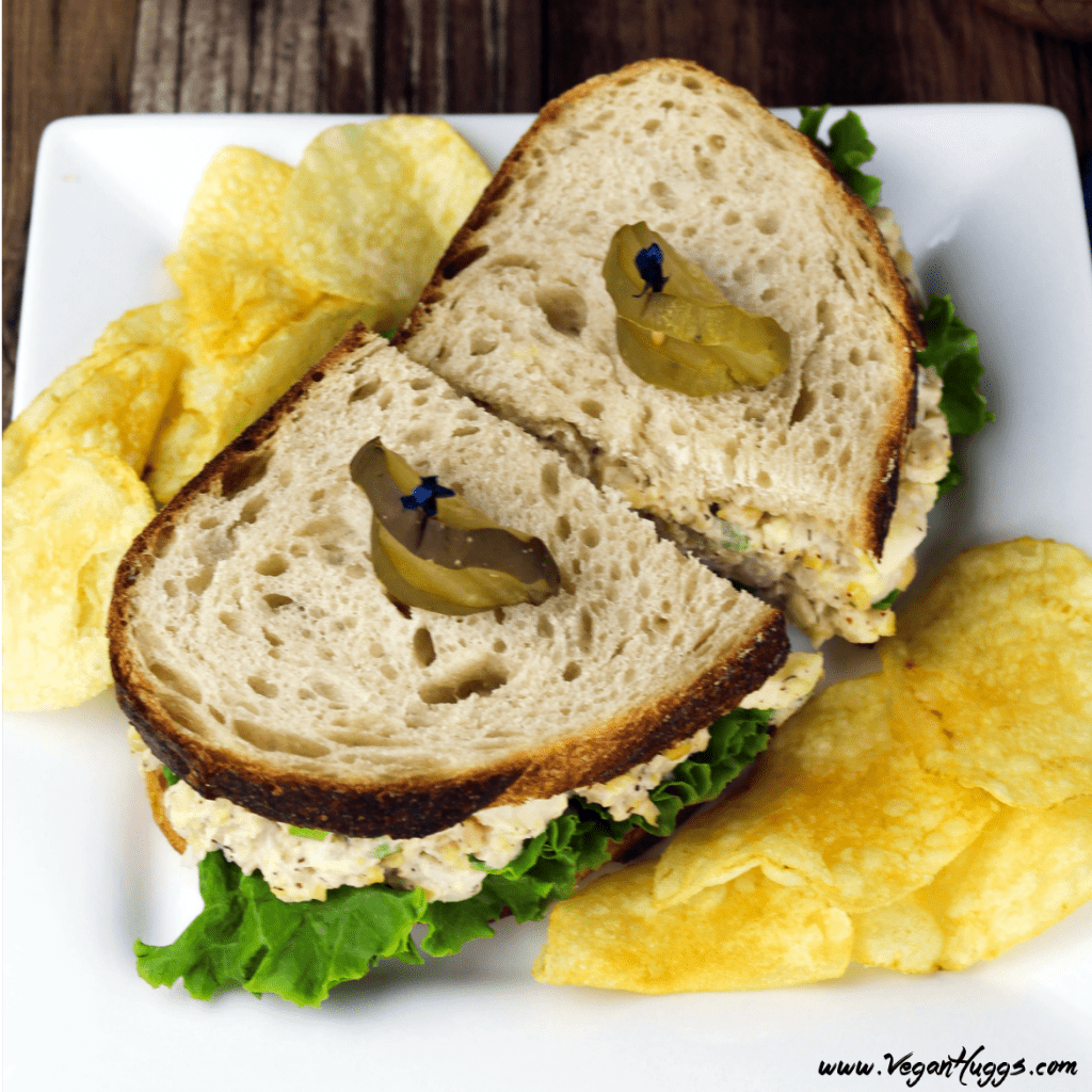 Overhead view of vegan tuna salad sandwich on a square plate. Topped with pickle slices.