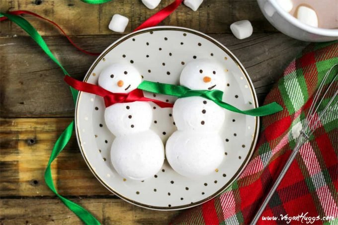 two snowmen meringue cookies on a polka dot plate. Hot cocoa on the side.