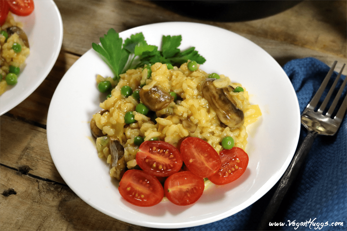 Vegan mushroom risotto on a white plate with fresh parsley and tomatoes on the side.
