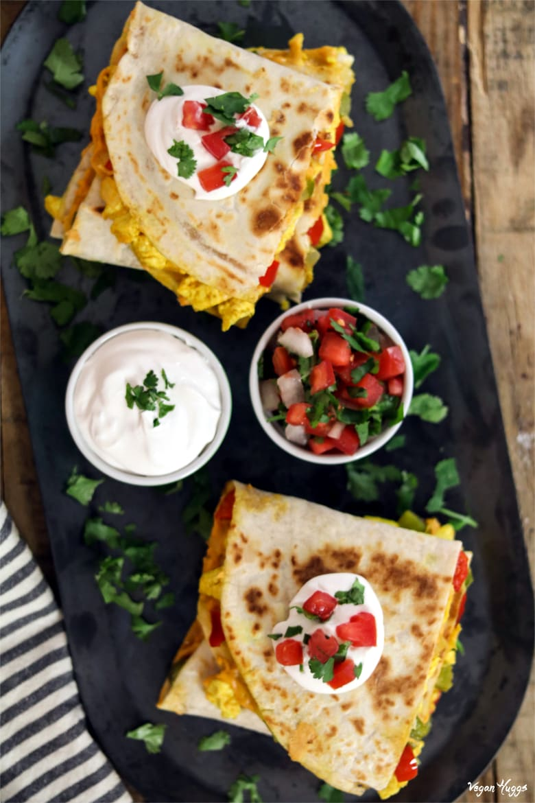 Vertical photo of vegan breakfast quesadilla with vegan sour cream and pico de gallo.